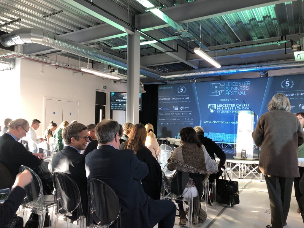 People sitting in rows of chairs waiting for a presentation at Leicester Business Festival 2019.
